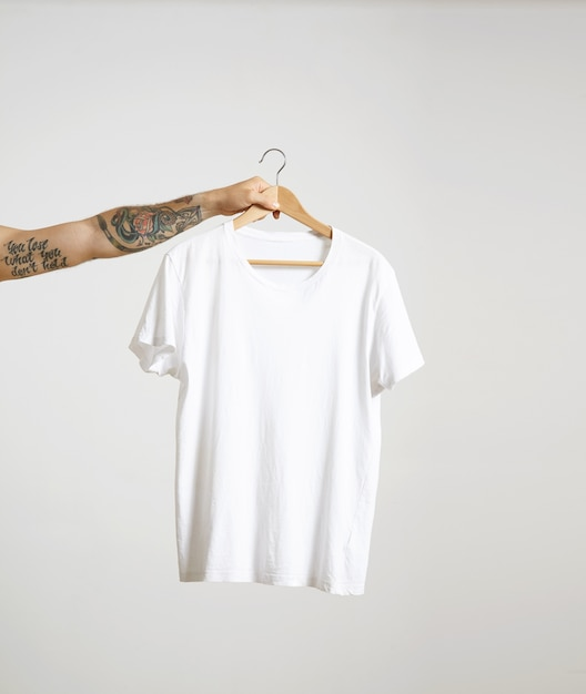 Татуированная рука байкера держит вешалку с пустой белой футболкой из тонкого хлопка премиум-класса, изолированной на белом Бесплатные Фотографии