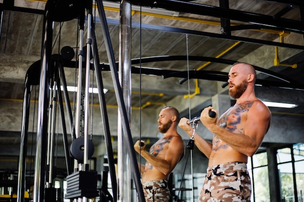 Tattooed fit man doing exercise at the gym Free Photo