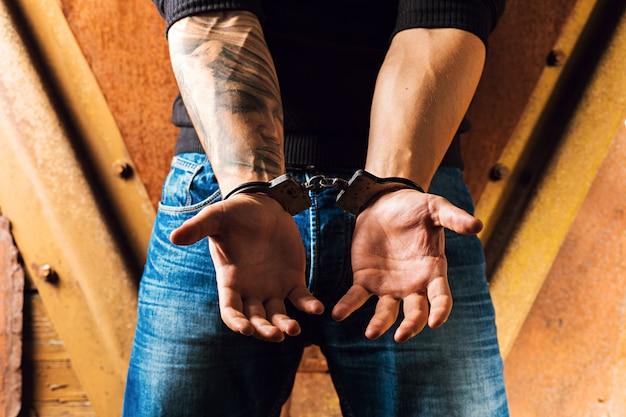 Tattooed hands of a criminal handcuffed Premium Photo