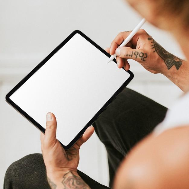 Татуированный человек работает над макетом экрана планшета Бесплатные Фотографии