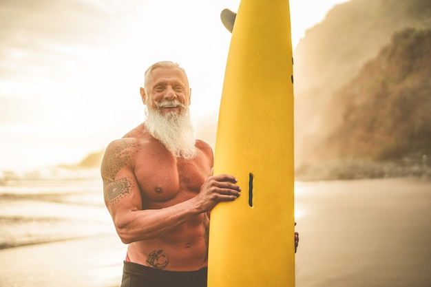Premium Photo Tattooed Senior Surfer Holding Surf Board On The Beach At Sunset Happy Old Guy Having Fun Doing Extreme Sport Joyful Elderly Concept Focus On His Face