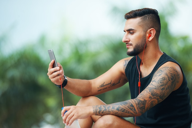 Tattooed sportsman with phone outdoors Free Photo