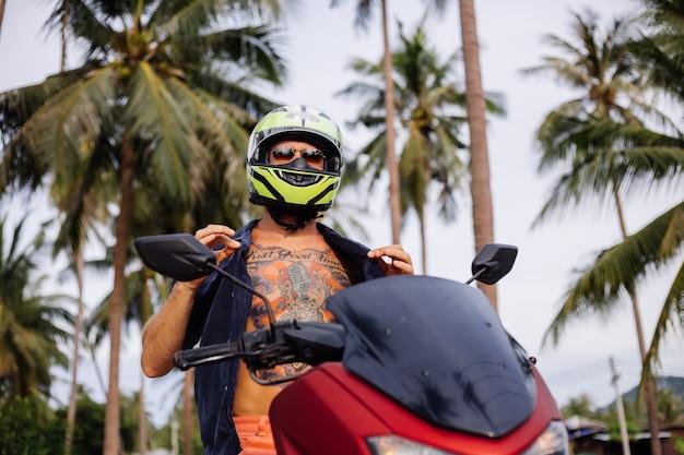 Uomo forte tatuato sul campo della giungla tropicale con una moto rossa Foto Gratuite