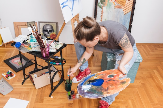 Tattooed woman holding palette and dipping paintbrush into water Free Photo