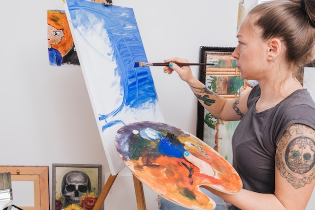Tattooed woman standing and painting blue picture on canvas Free Photo