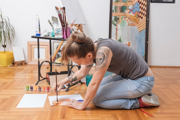Tattooed young woman sitting on floor and painting Free Photo