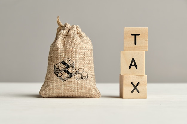 Tax concept next to a bag of money. close up. Premium Photo