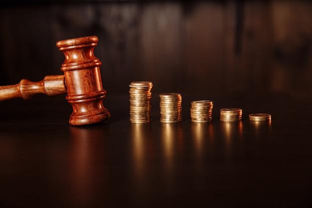 Концепция уплаты налога. стек монет с деревянным молотком судьи. Premium Фотографии