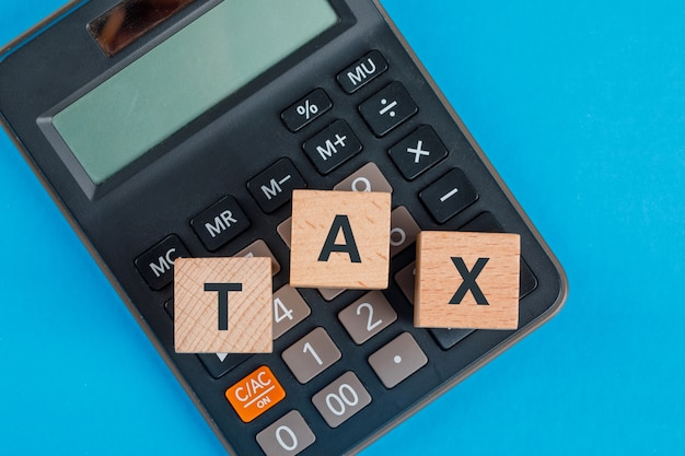 Tax planning concept with wooden cubes on calculator on blue table flat lay. Free Photo
