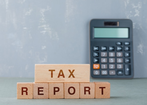Концепция налогового отчета с деревянными блоками со словами на нем вид сбоку. Бесплатные Фотографии