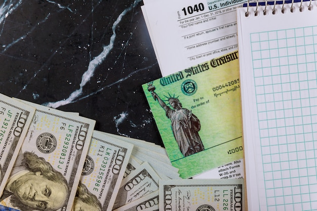 Tax return and refund check us tax form, dollar cash and blank notebook 1040 individual tax form Premium Photo