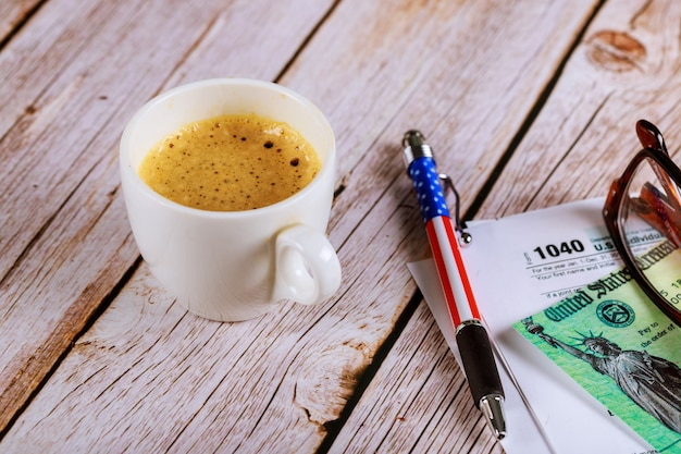 Tax season an office with a glasses and pen on income tax return 1040 form with black coffee Premium Photo