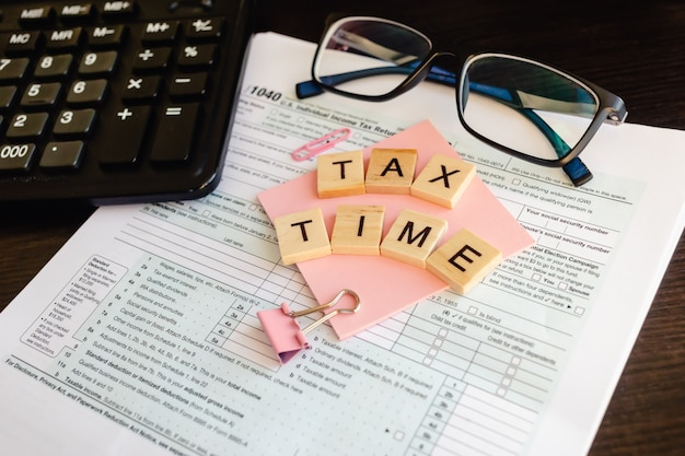 Tax time - wooden letters, tax form with sticker, glasses and calculator. Premium Photo