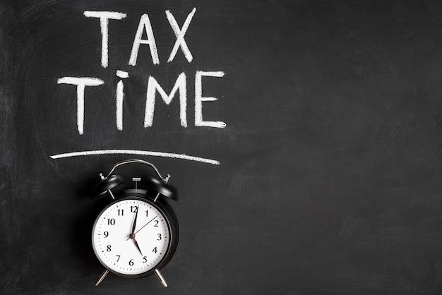Tax time word written over alarm clock on chalkboard Premium Photo