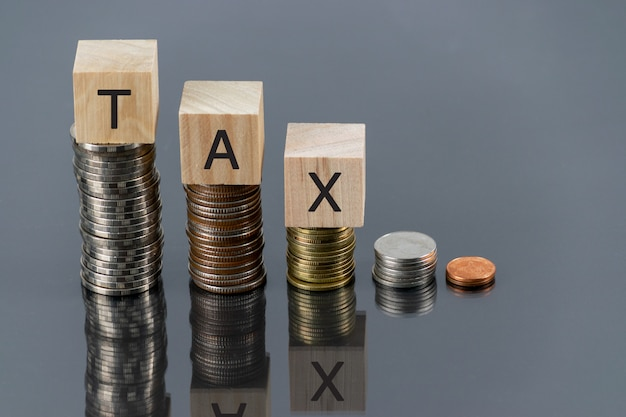 Tax wooden cube with stack of coin on table with reflector Premium Photo