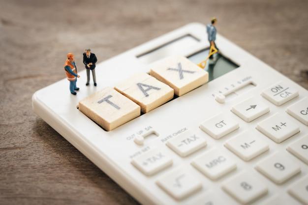ミニチュアの人々電卓でその年のキューの年収(tax)を支払います。 Premium写真
