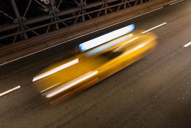 Taxi on bridge at night with motion blur Free Photo