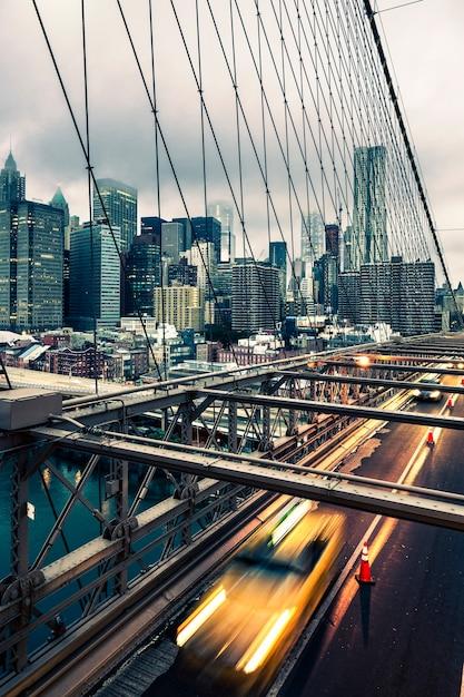 ニューヨークのブルックリン橋を渡るタクシー、マンハッタンのスカイラインを背景に 無料写真