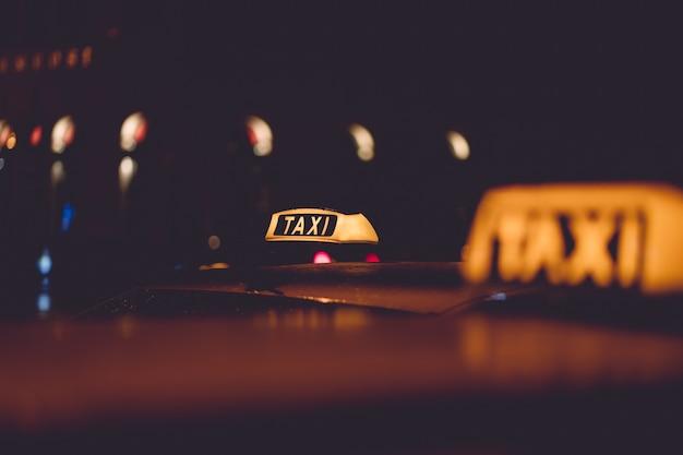 Segno di taxi su sfondo sfocato di notte della città Foto Gratuite