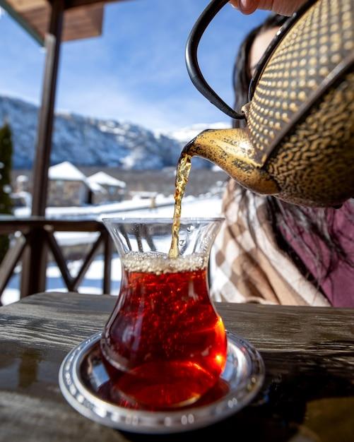 山を背景に黒茶を注ぐ女性 無料写真