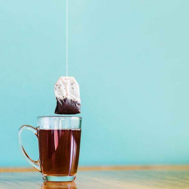Tea bag and glass cup Free Photo