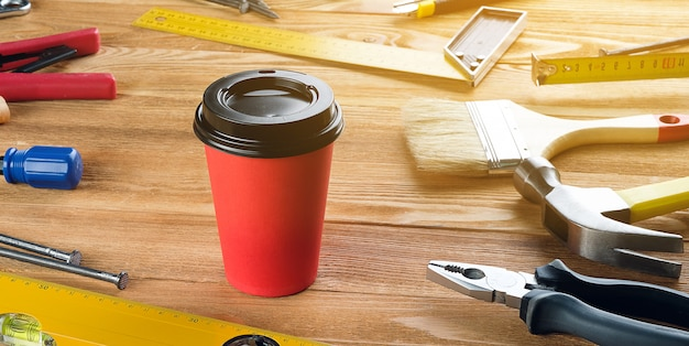 Tea or coffee in a disposable cup, tools for professional construction or home repair, on a wooden table. a snack or break at the workplace of a foreman or carpenter. tinted photo. banner. Premium Photo