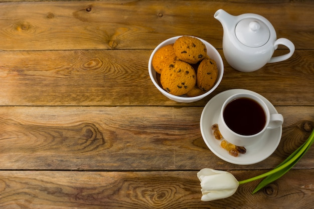 Tea cup, cookies  and teapot on wooden background, copy space Premium Photo