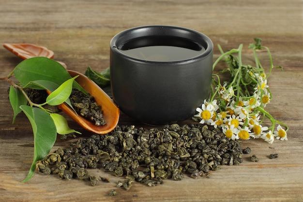 Чай - чашка, зеленый лист и ромашка Premium Фотографии