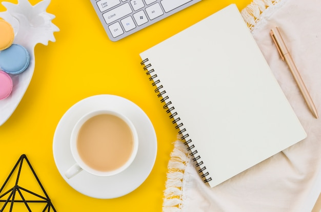 Tea cup; macaroons; spiral notebook; pen on tablecloth against yellow background Free Photo