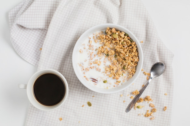 Tea cup; oat meals bowl; spoon on tablecloth Free Photo
