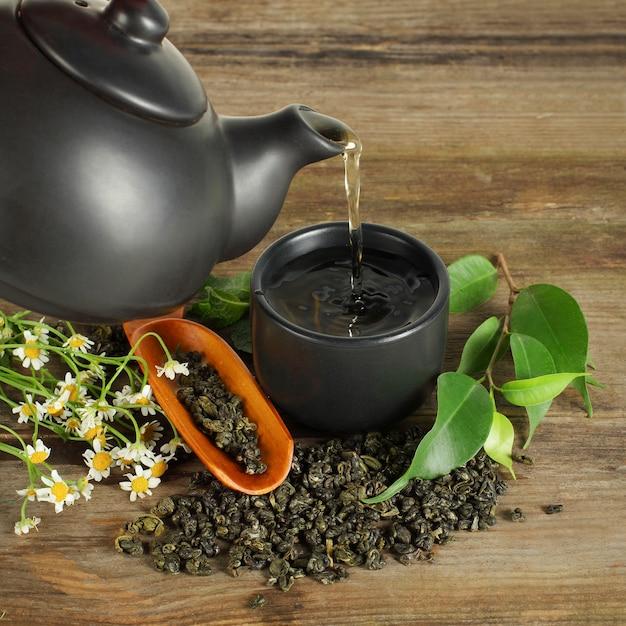 お茶-カップ、ティーポット、緑の葉 Premium写真