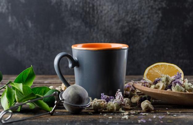 Tè in una tazza con lime, filtro, erbe, limone, lime vista laterale sulla superficie scura e in legno Foto Gratuite