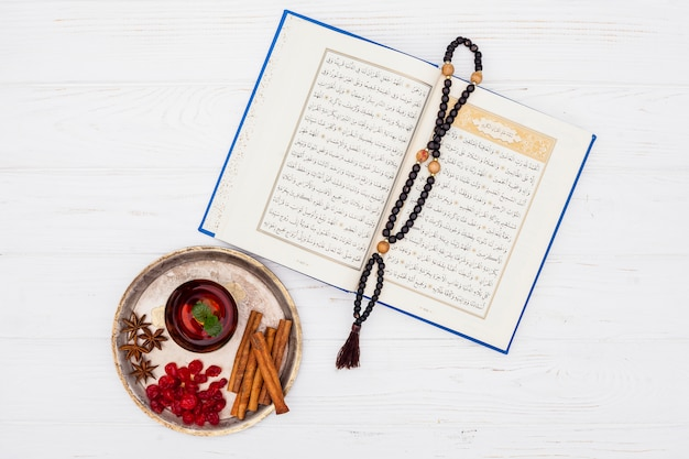 Tea cup with quran and beads on table Free Photo