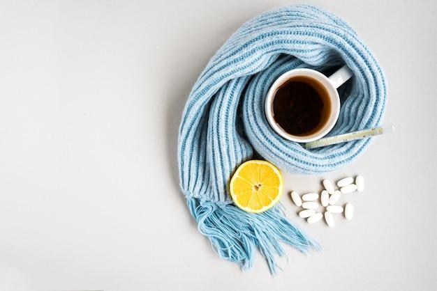灰色の壁に温度計、青いスカーフ、丸薬、レモンが入ったティーカップ。インフルエンザの季節、病気。 Premium写真
