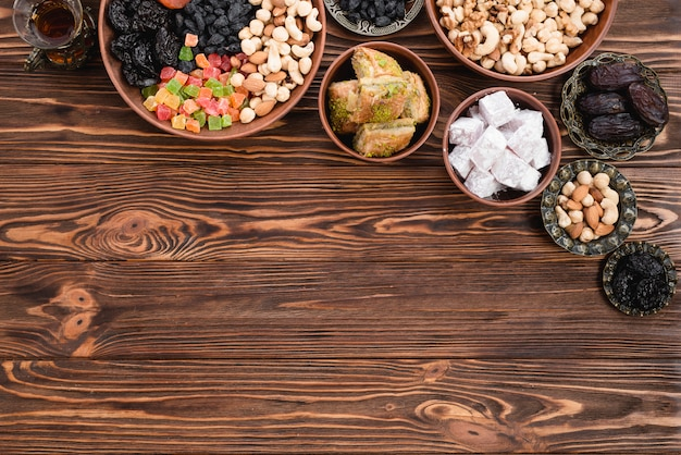 Tea; dried mixed fruits; nuts; lukum and baklava on earthen and metallic bowl on wooden desk Free Photo