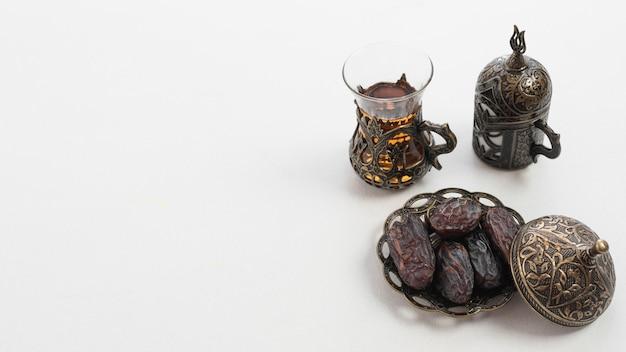 Стакан чая и сушеные сочные фрукты финиковой пальмы или курма на рамадан еду на белом фоне Premium Фотографии