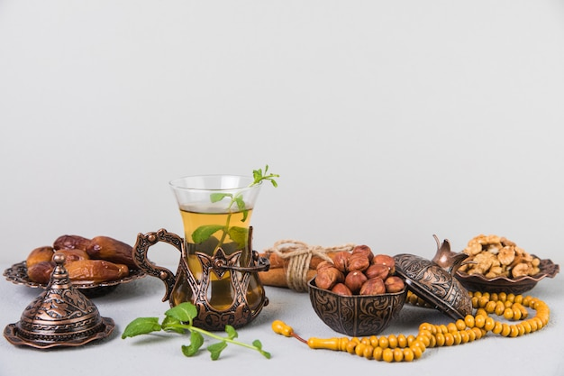 Tea glass with dates fruit, beads and nuts Free Photo