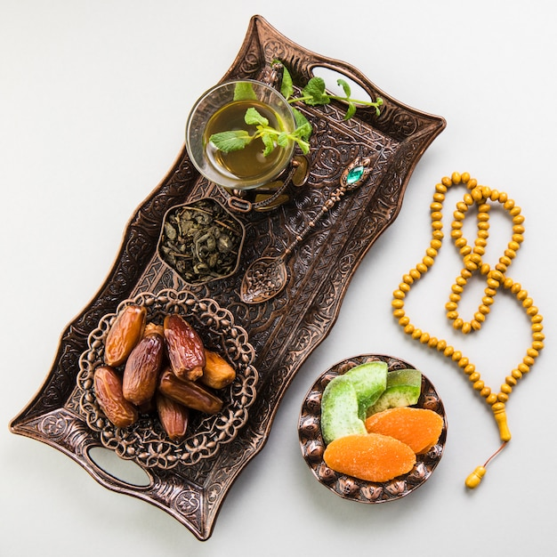 Tea glass with dates fruit and beads on tray Free Photo