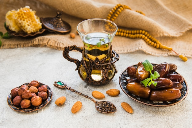 Tea glass with dates fruit and different nuts Free Photo