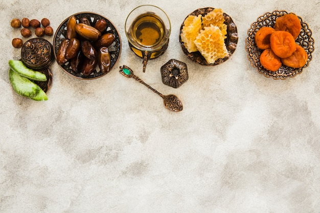 Tea glass with different dried fruits and honeycomb Free Photo