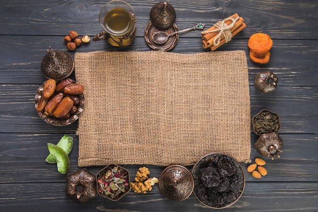 Tea glass with different dried fruits, nuts and canvas Free Photo