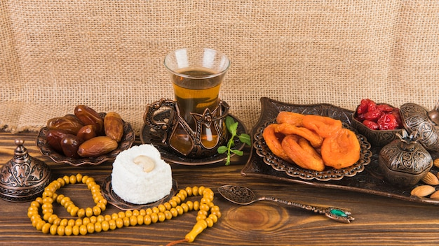 Tea glass with dried fruits and beads on wooden table Free Photo