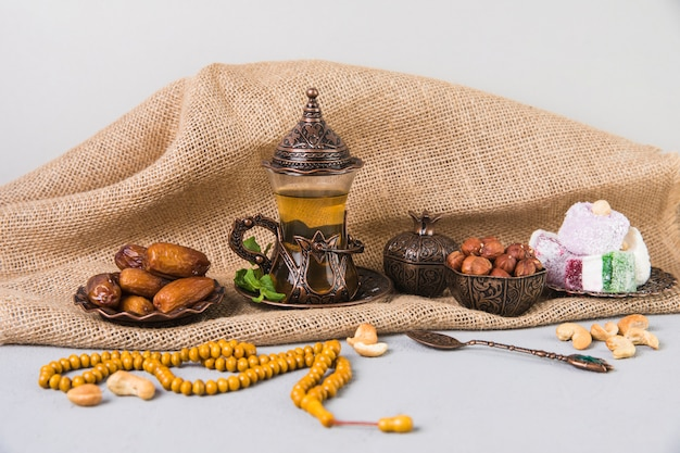 Tea glass with eastern sweets and beads Free Photo