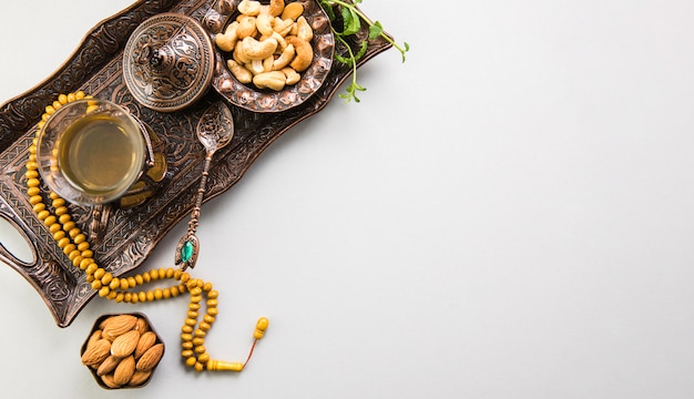 Tea glass with nuts and beads on tray Free Photo