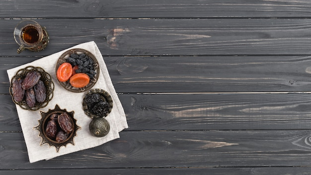 Tea glass with whole juicy dates and dried fruits on napkin over the wooden desk Free Photo