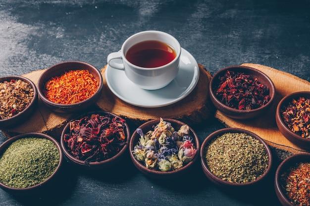 Erbe di tè in ciotole con tronchi di legno e una tazza di tè veduta dall'alto su uno sfondo scuro con texture. spazio per il testo Foto Gratuite