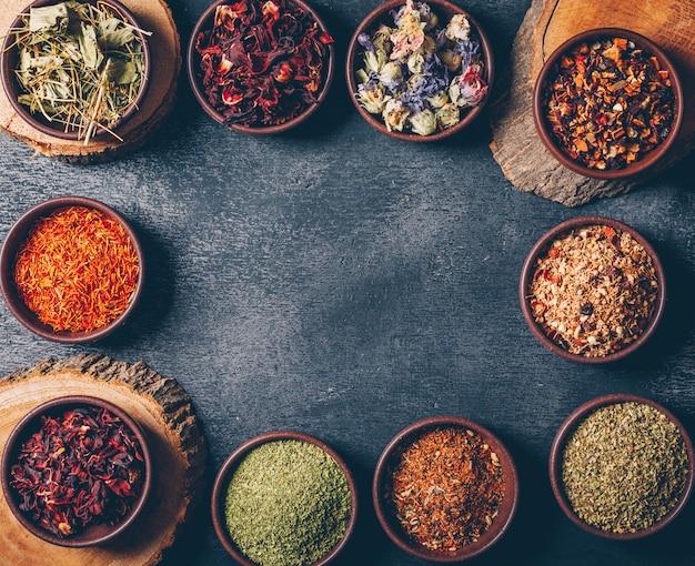 Le erbe del tè in ciotole con il piano di mozziconi di legno giacciono su uno sfondo scuro con texture. spazio per il testo Foto Gratuite