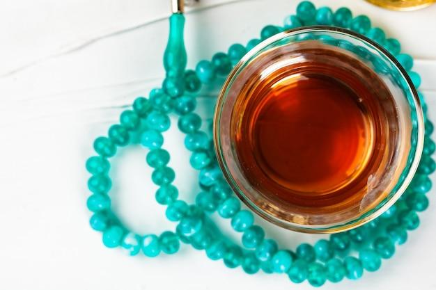 ガラスのカップでお茶と白い背景の上のビーズを祈る Premium写真