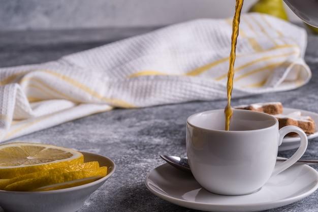 テーブルの上のカップ、クッキー、レモン、梨にお茶を注ぐ Premium写真