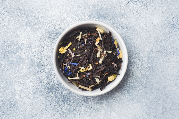 Tea leaves for brewing in bowl on a gray background. Premium Photo